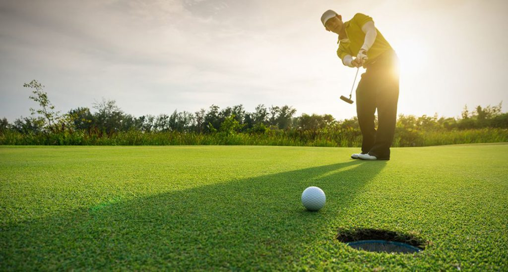 Man with golf club and golf ball